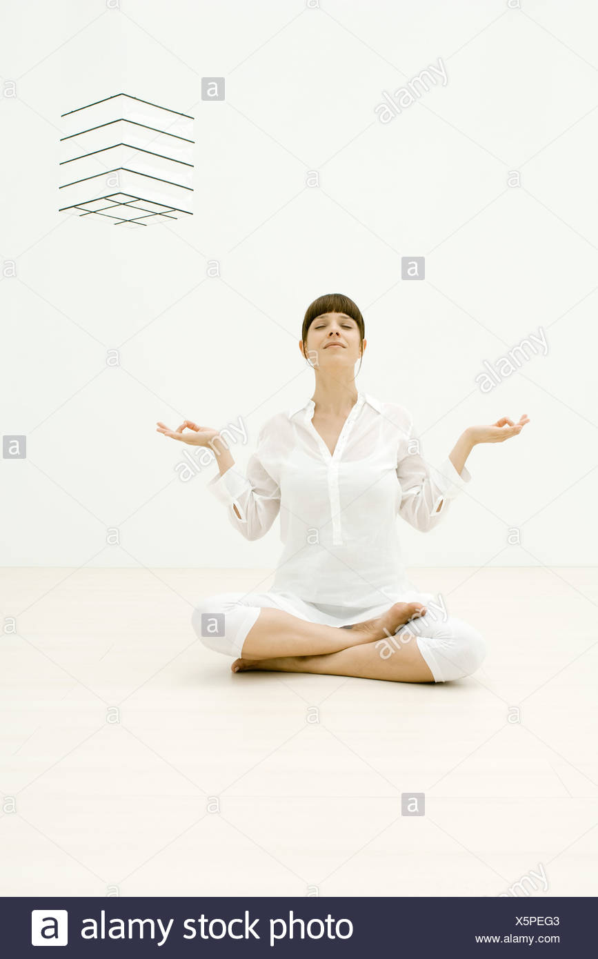 Woman sitting in lotus position, eyes closed Stock Photo