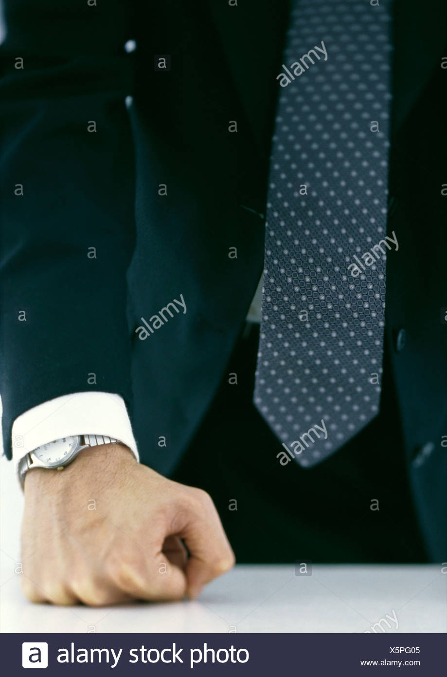 Businessman pressing fist against table, close-up - Stock Image
