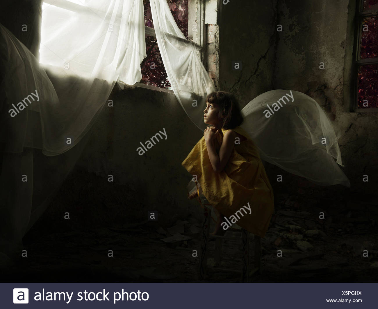 Girl sitting on a chair looking out of a window in an abandoned house - Stock Image