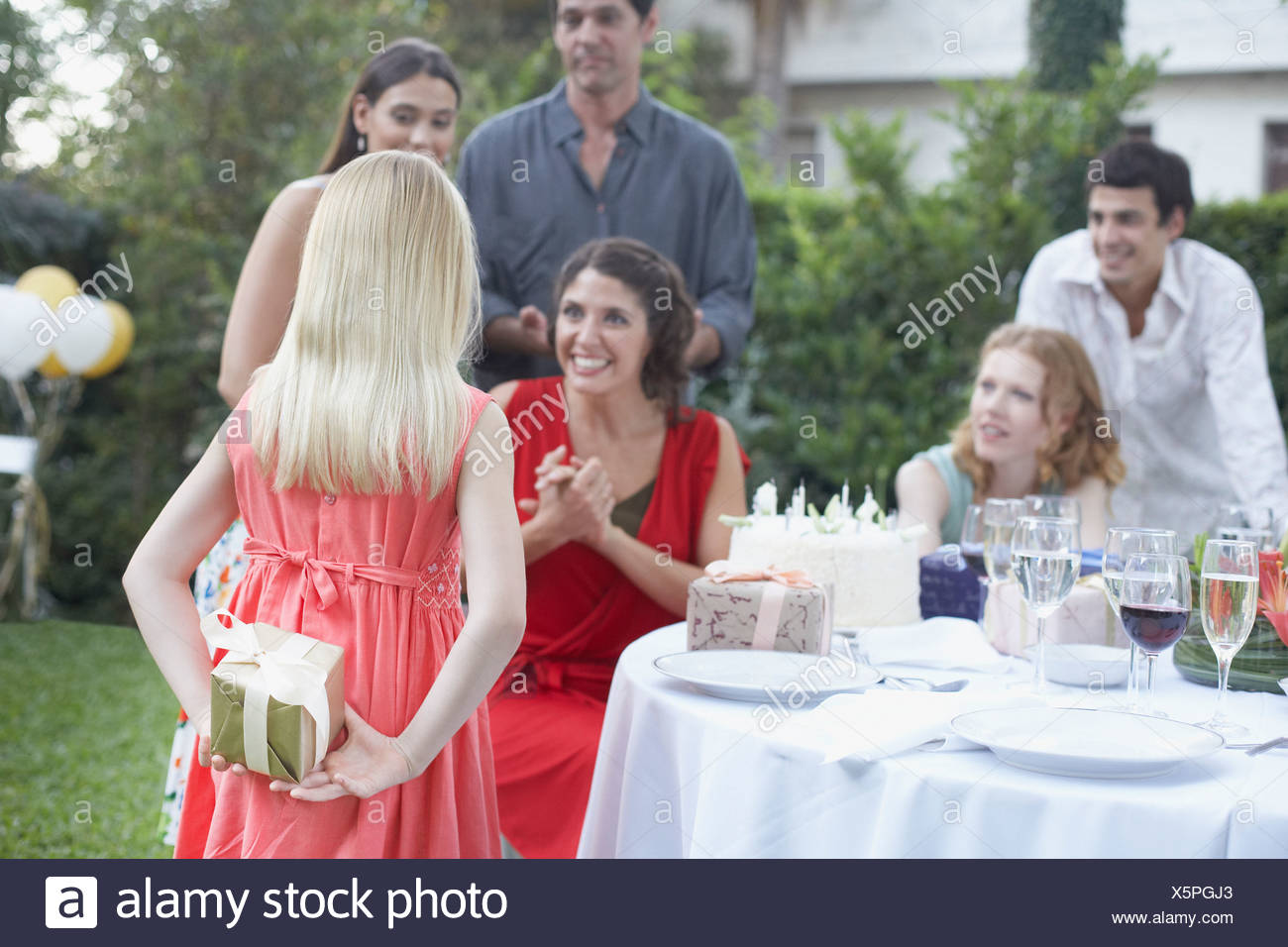 Young girl at outdoor birthday party about to give gift to woman with partygoers watching and smiling - Stock Image