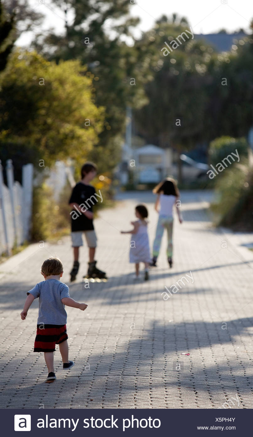 A group of kids are roller blading and walking down an alley. Stock Photo