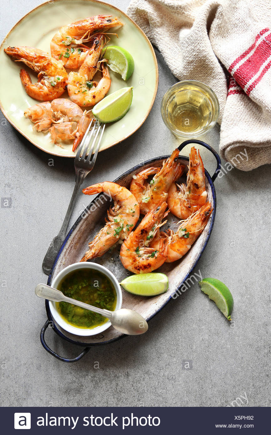 Grilled prawn with garlic salsa sauce on an enamel plate.Top view - Stock Image