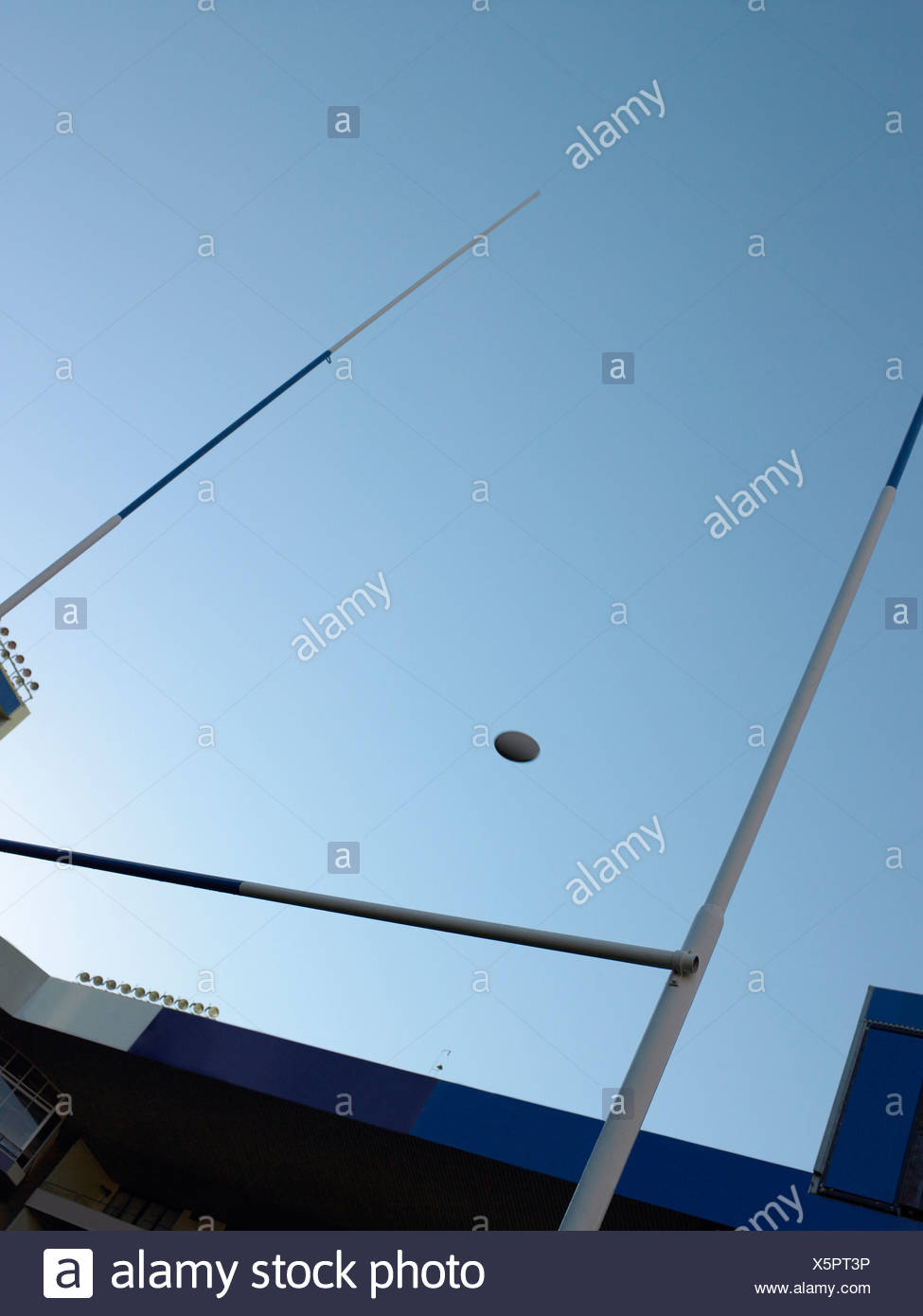 Rugby ball over a rugby post - Stock Image
