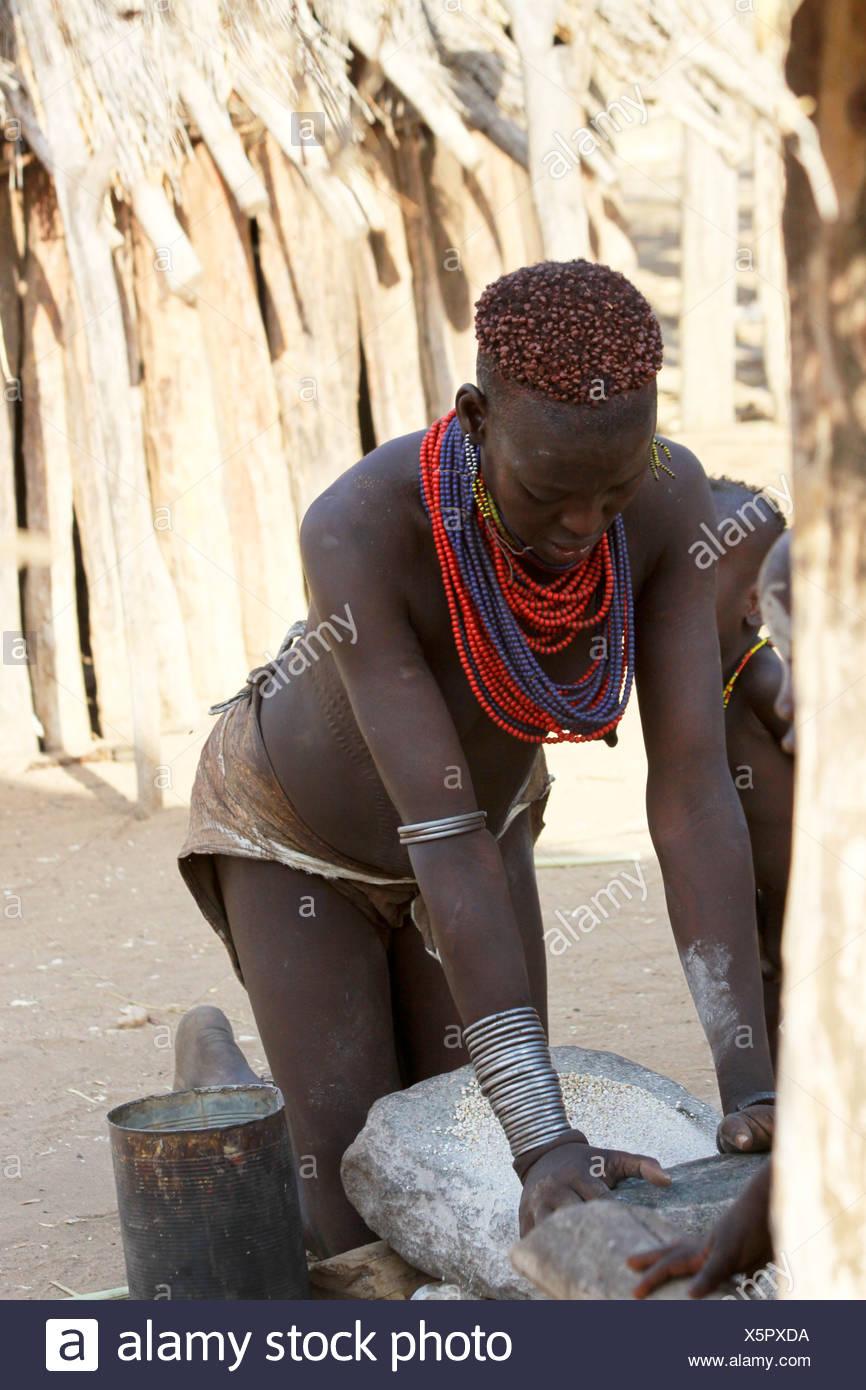 Africa, Ethiopia, Omo Valley, Woman of the Karo tribe grinding grain to four - Stock Image