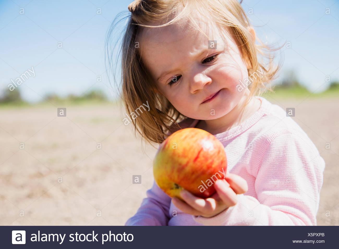 Portrait of girl (2-3) holding apple - Stock Image