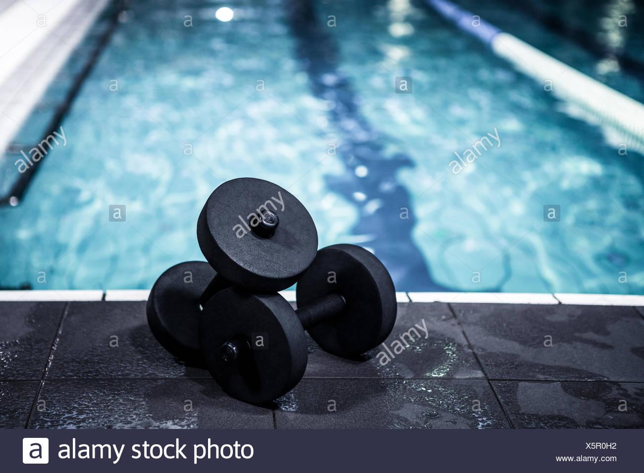 Foam dumbbells beside the pool - Stock Image