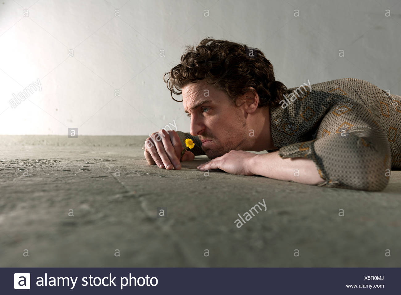 Mid adult man lying on floor and smelling flower - Stock Image