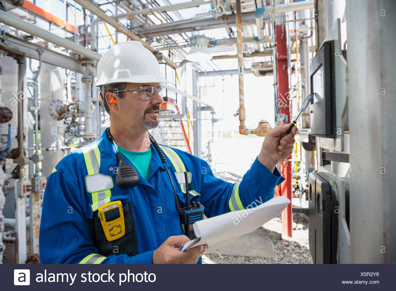 Male worker checking equipment at gas plant - Stock Image