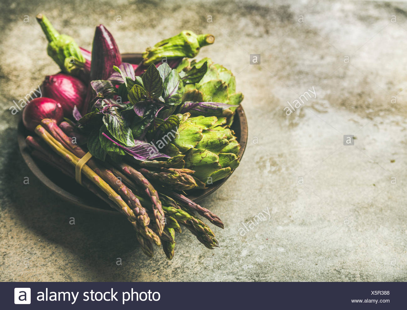 Green and purple vegetables on plate over concrete background, selective focus, copy space. Local produce for healthy cooking. Eggplans, beans, kale,  - Stock Image
