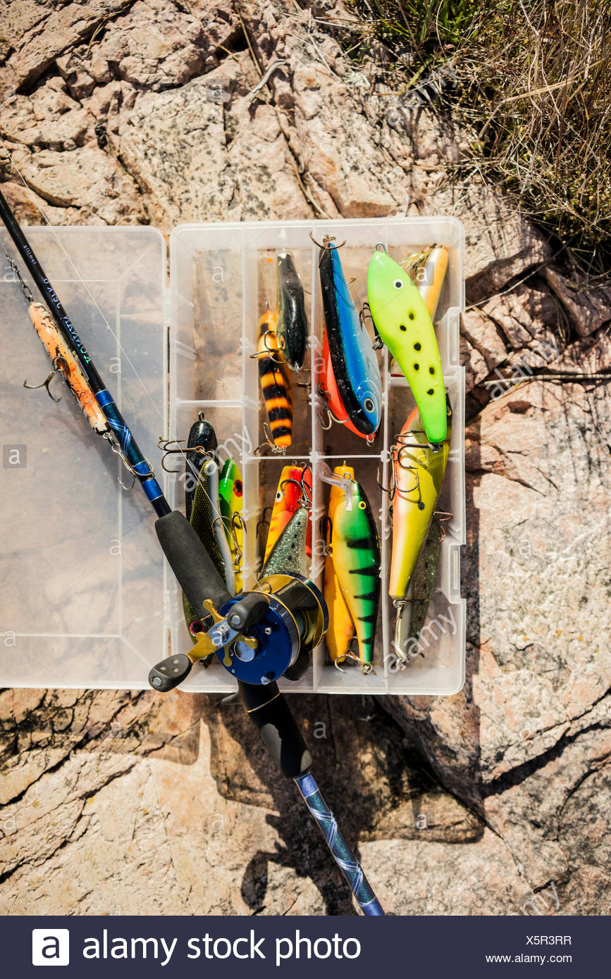 Sweden, Box of fishing tackles and fishing rod on rock - Stock Image