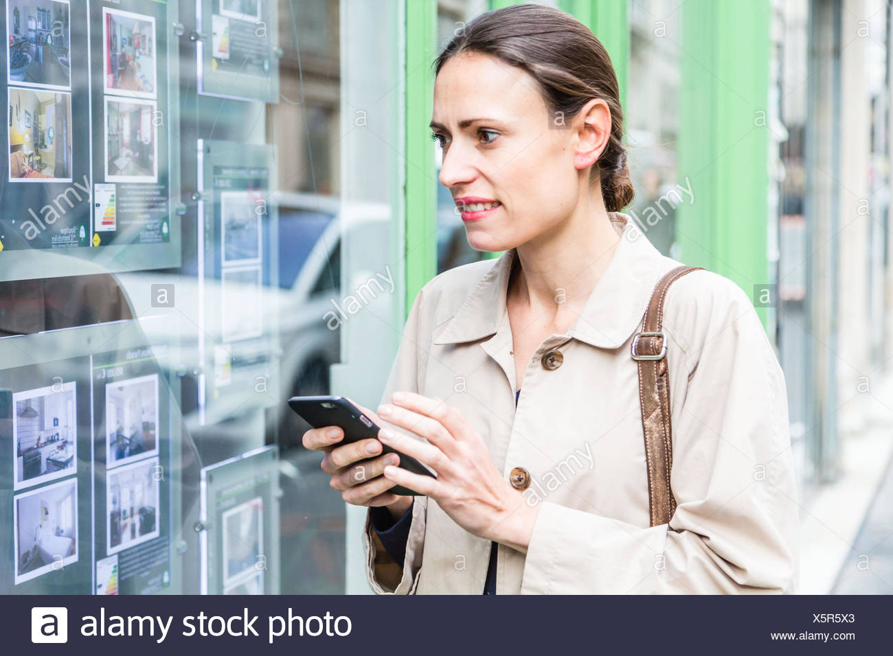 Woman looking for ads in a real estate agency. - Stock Image