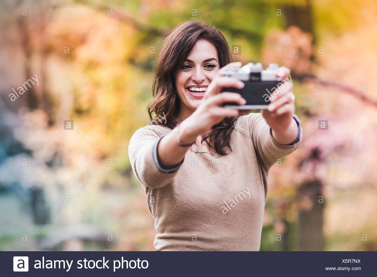 Young woman taking selfie with SLR camera in autumn forest - Stock Image