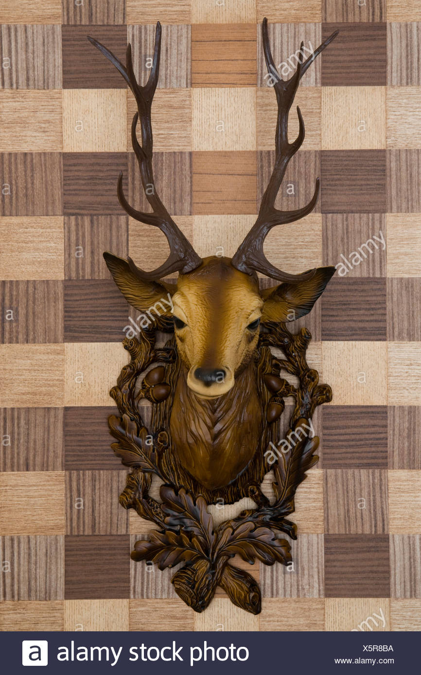 Plastic deer head mounted on imitation wood wallpaper, frontal view - Stock Image
