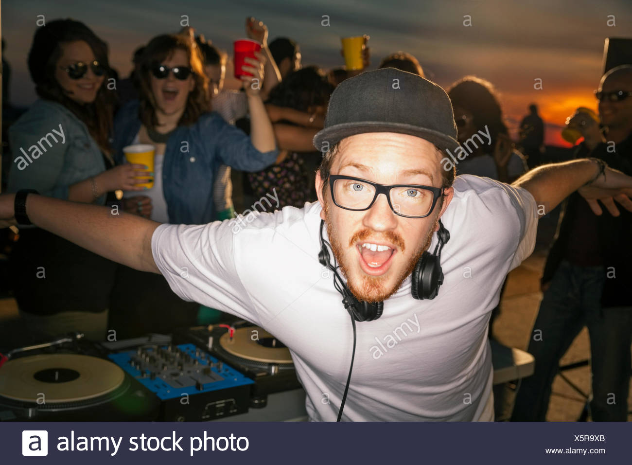 Portrait of enthusiastic DJ at rooftop party - Stock Image