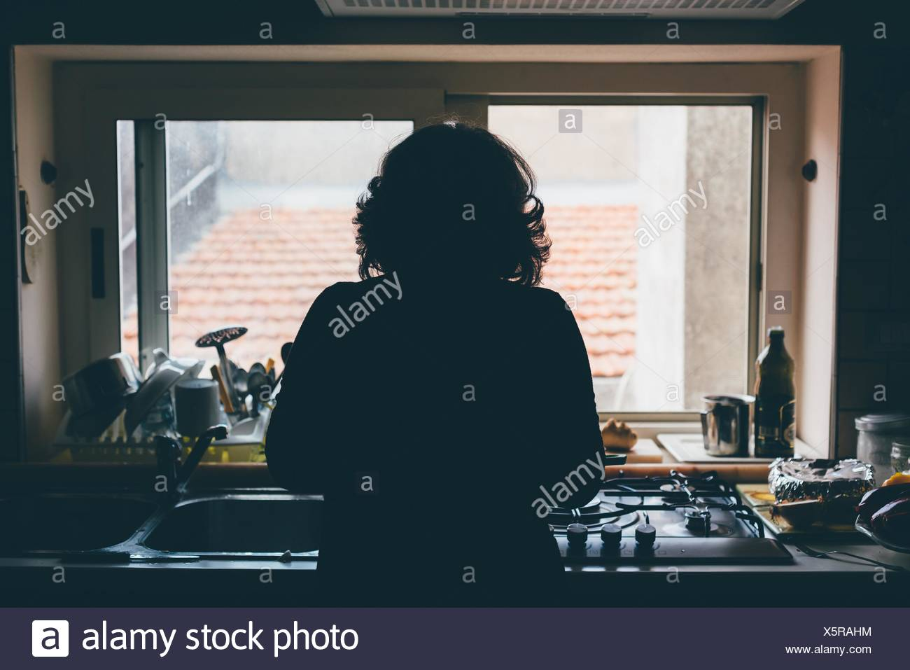 Rear silhouetted view of woman standing in front of kitchen sink - Stock Image