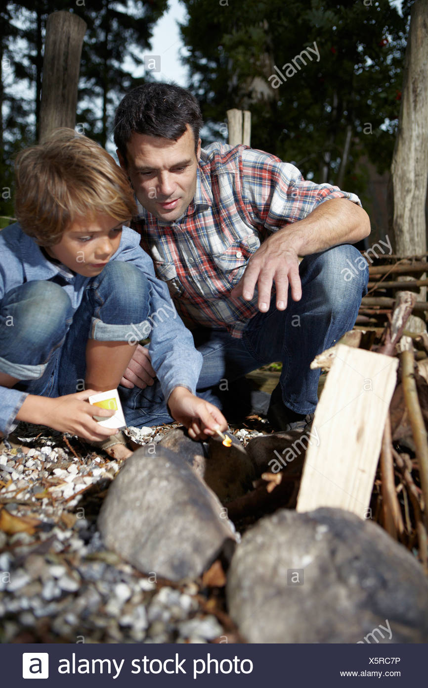 Father and son lighting fire outdoors - Stock Image