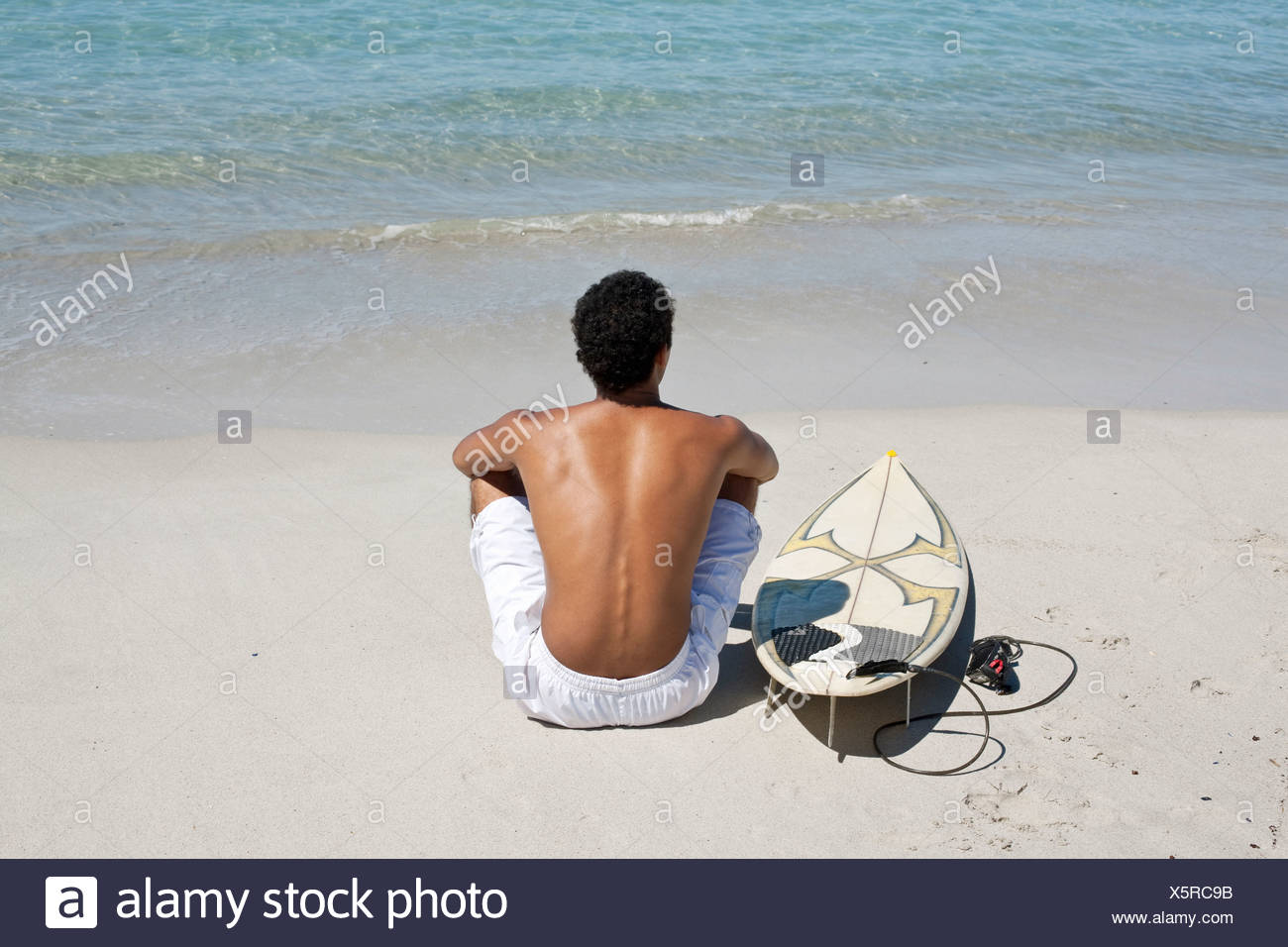 Rear view of young man sitting on beach with surfboard - Stock Image