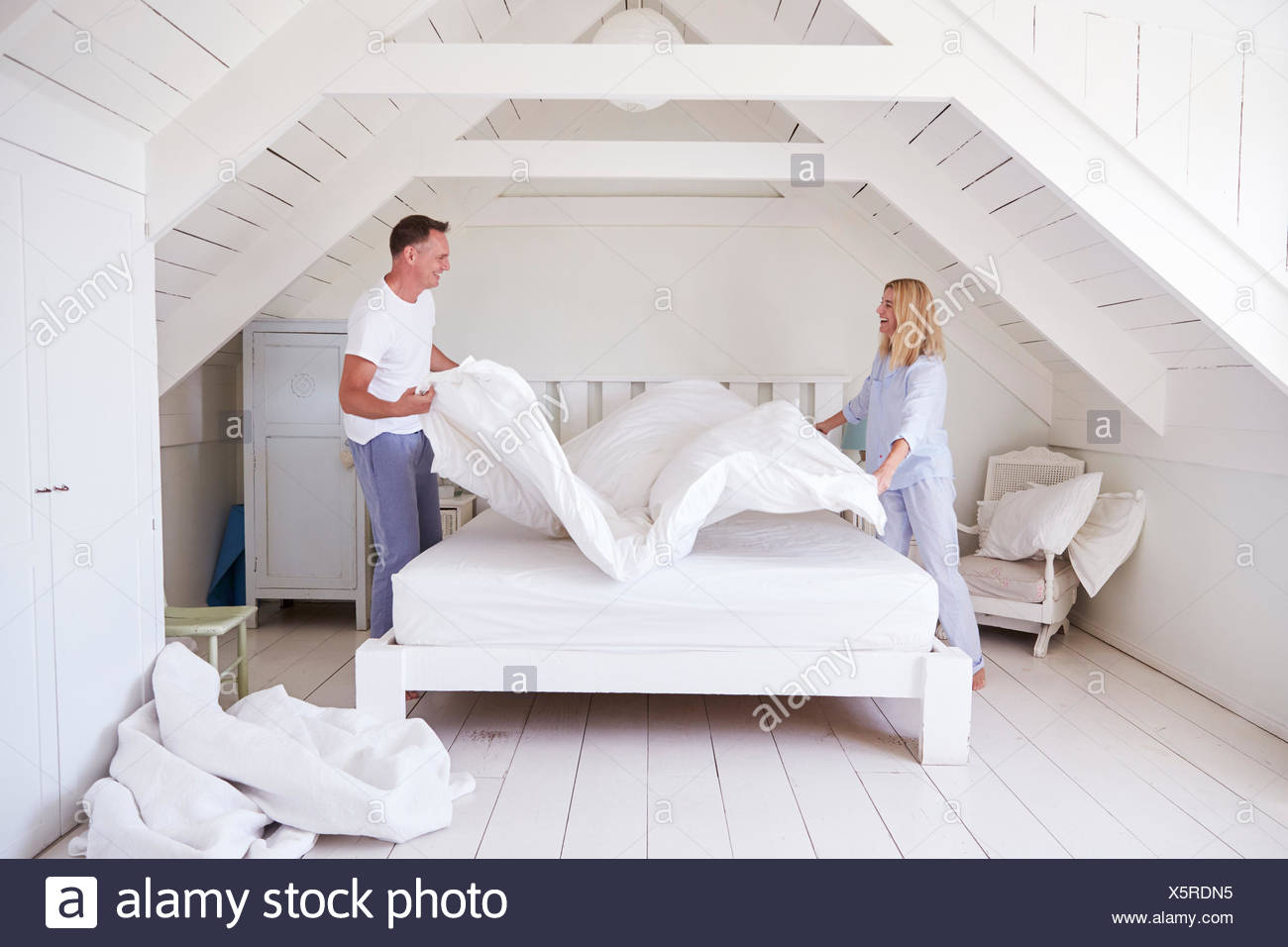 Couple Wearing Pajamas Making Bed In Morning - Stock Image