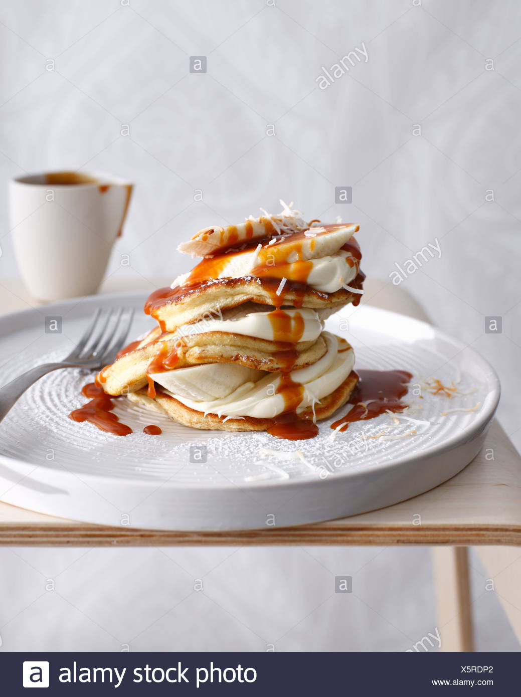 Plate of coconut pancakes with cream - Stock Image