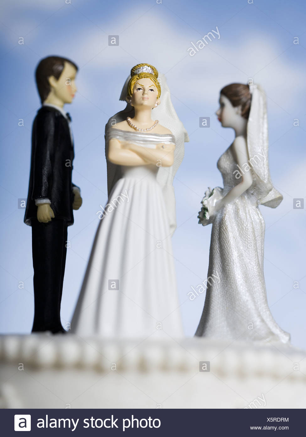 Wedding cake visual metaphor with figurine cake toppers - Stock Image