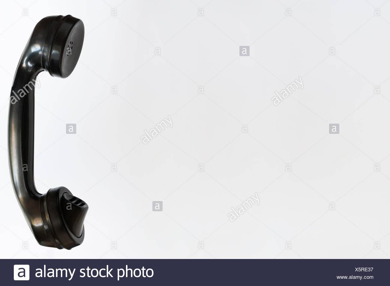 Alter schwarzer Telefonhoerer vor weissem Hintergrund. - Stock Image
