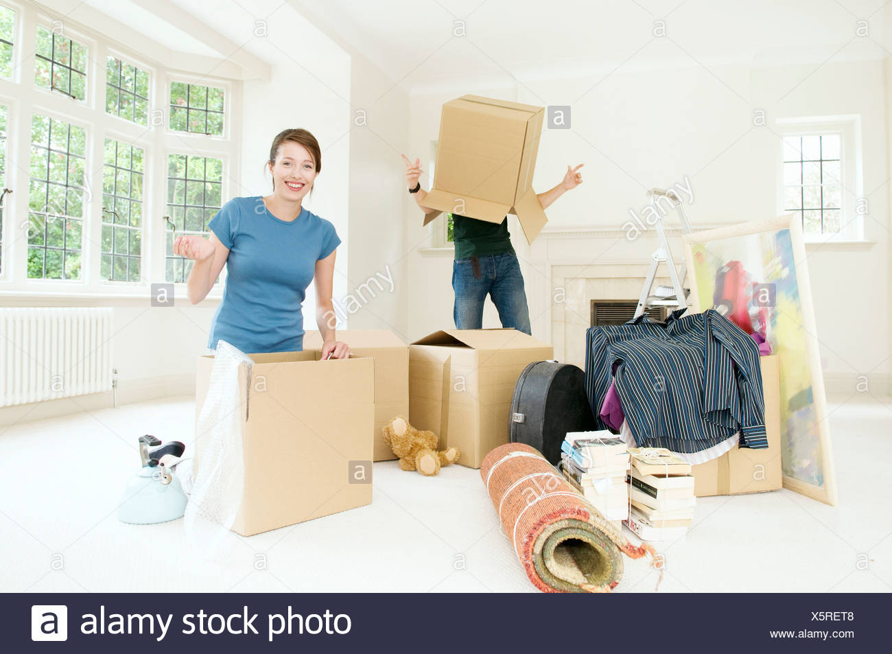 A couple having fun moving home - Stock Image