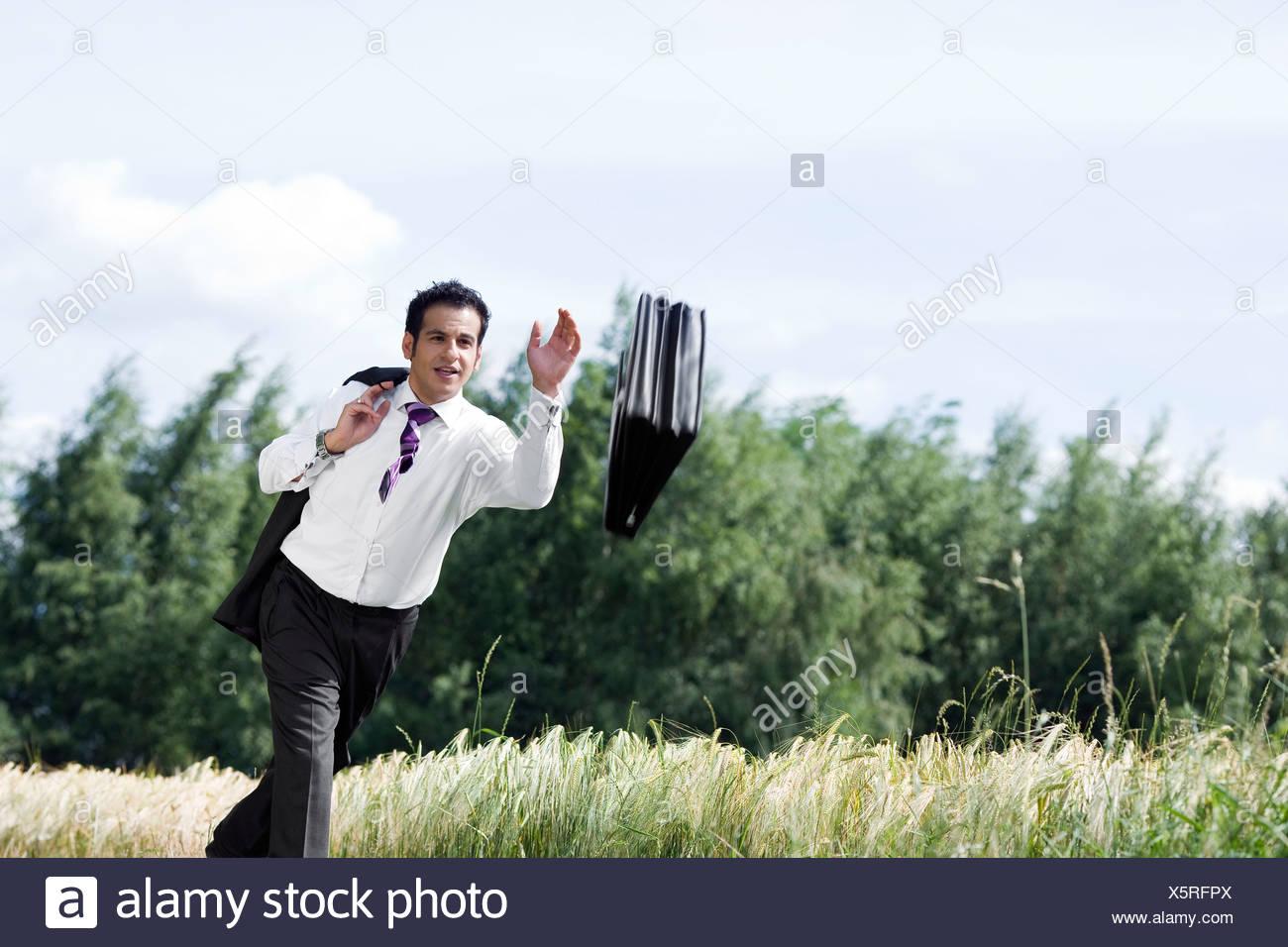 man throwing briefcase - Stock Image