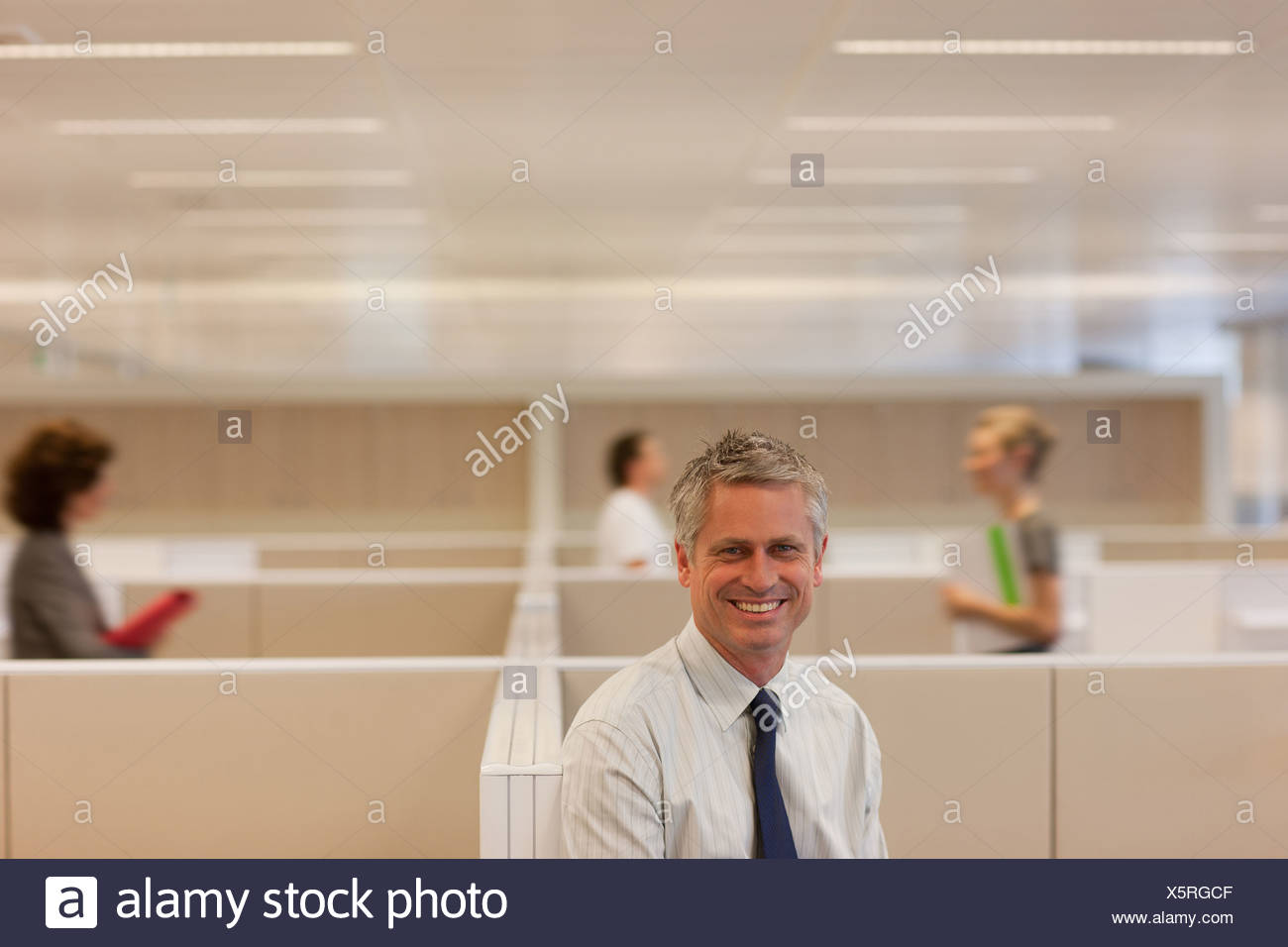 Businessman standing in office cubicle - Stock Image