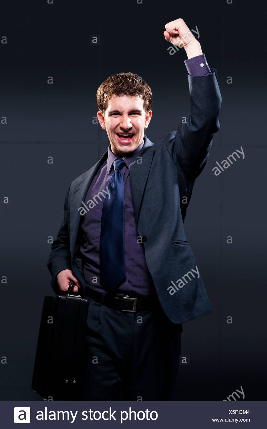 Business man with briefcase and arm up smiling - Stock Image