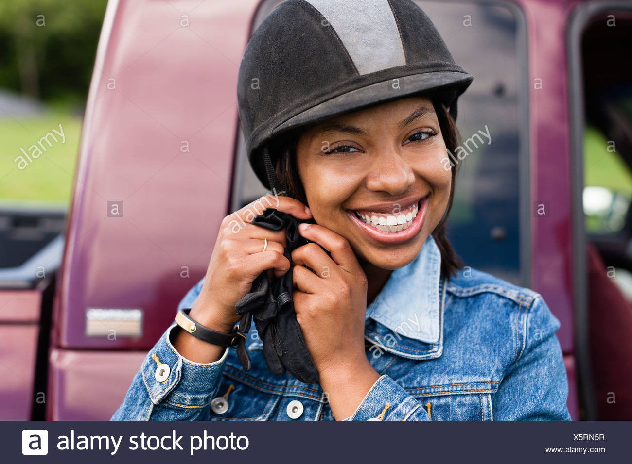Horse rider putting on riding hat Stock Photo