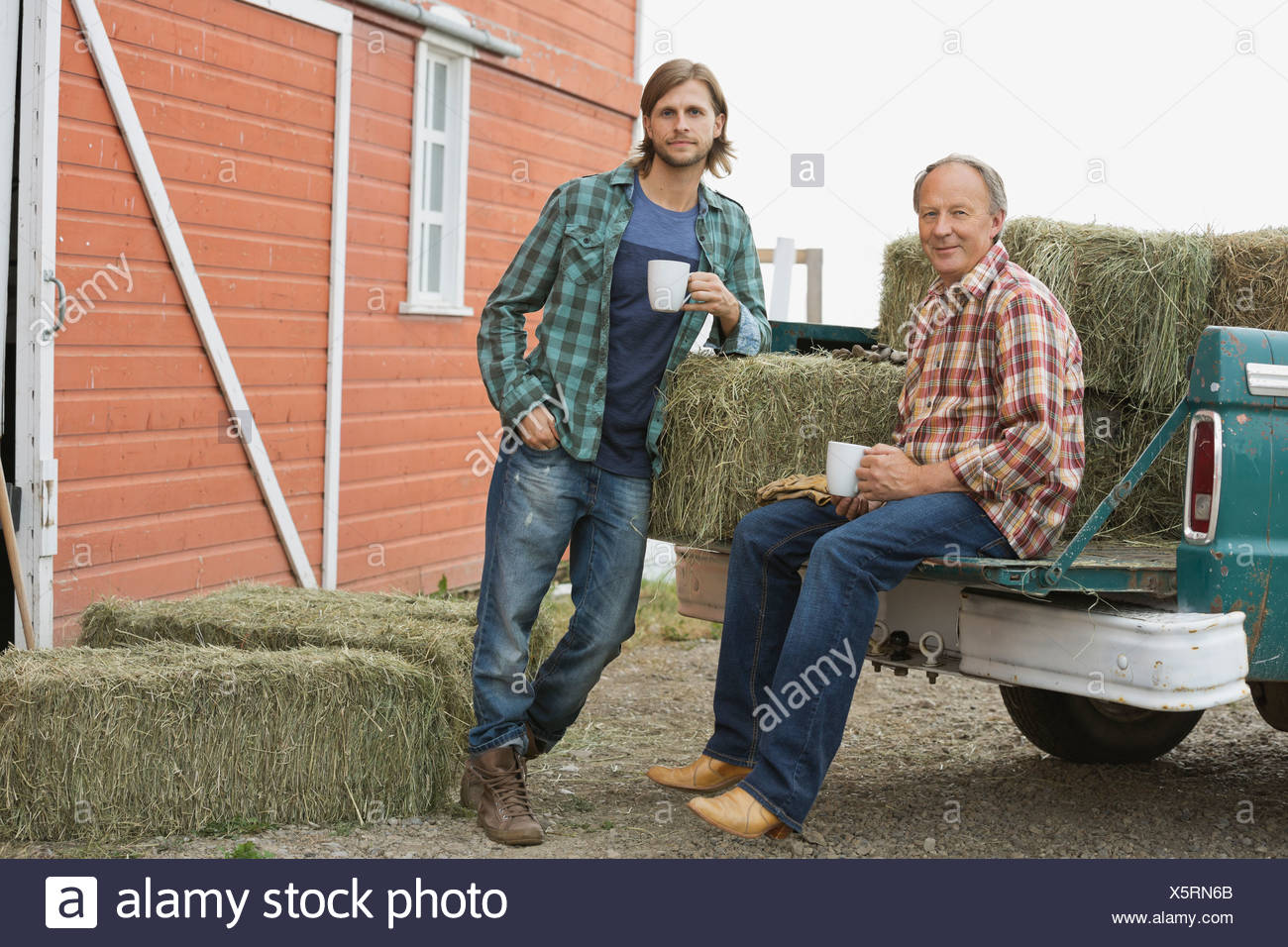 Father and son having coffee by pick-up truck with hay bales Stock Photo