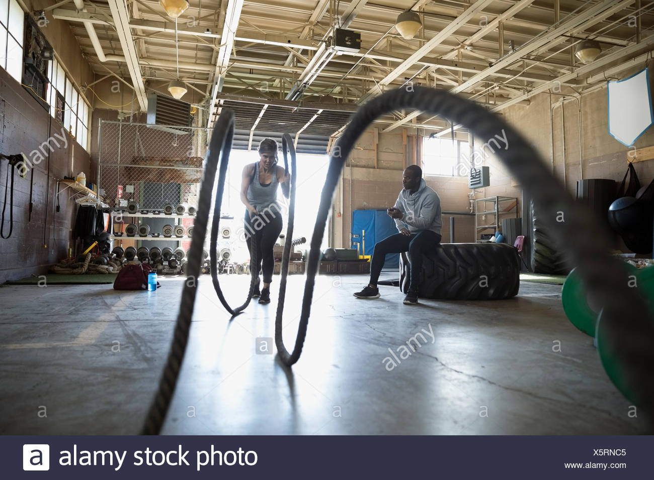 Male personal trainer watching female client doing crossfit battling ropes exercise in gym - Stock Image