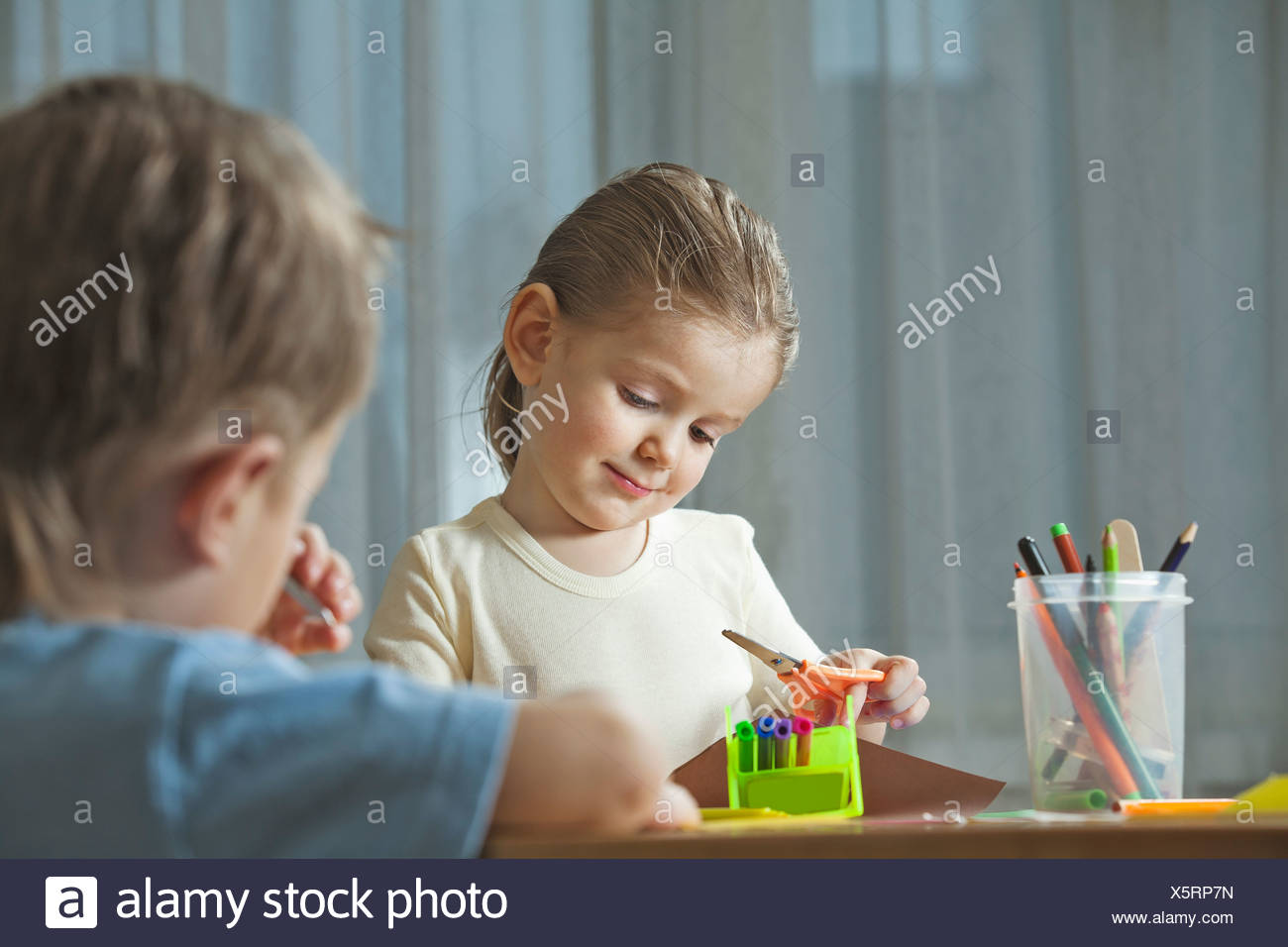 young girl and young boy doing handicraft together - Stock Image