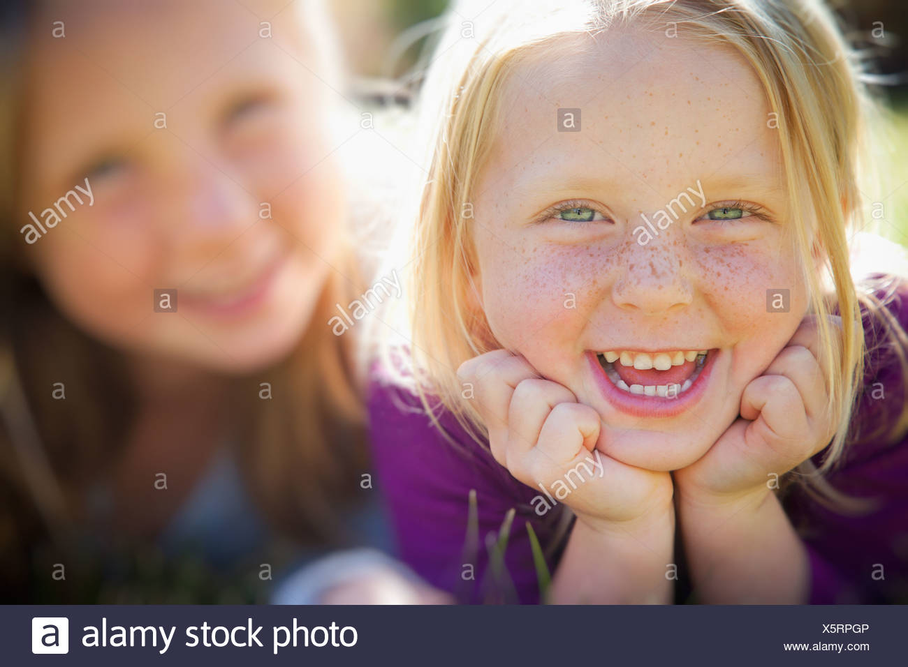 Two young girls, with blue eyes and blonde hair. Lying on the grass. Close up. - Stock Image