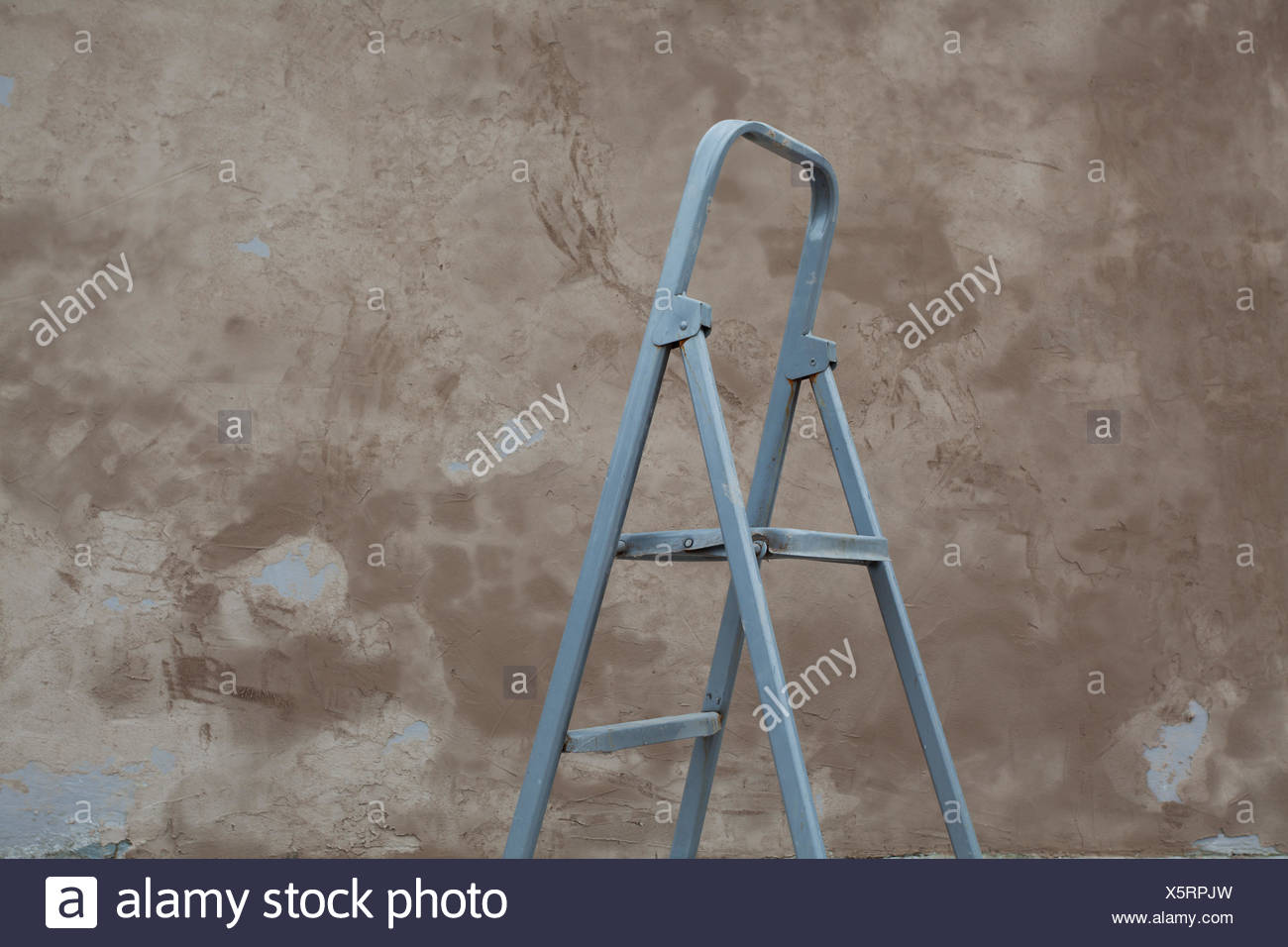 grey ladder and a grungy wall - Stock Image
