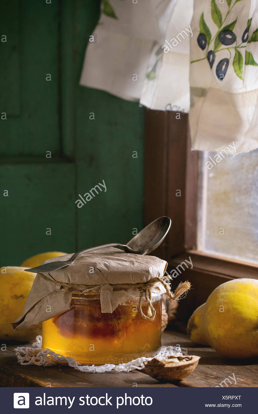 Three juicy quinces, walnuts and jar of honey over wooden table near window with bright sunlight. With green wooden wall at back - Stock Image