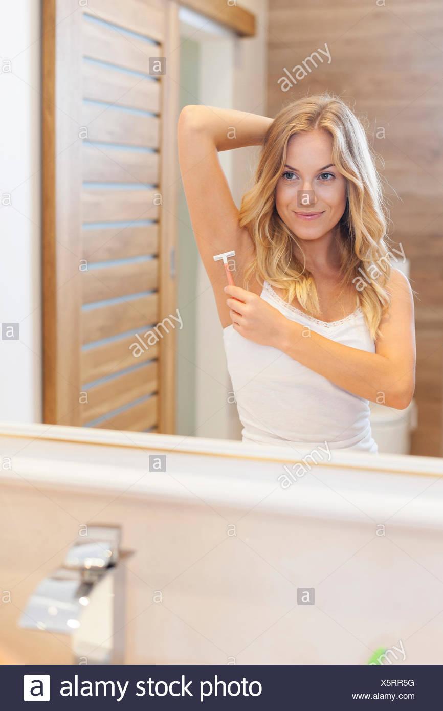 Woman shaving armpit in bathroom. Debica, Poland - Stock Image
