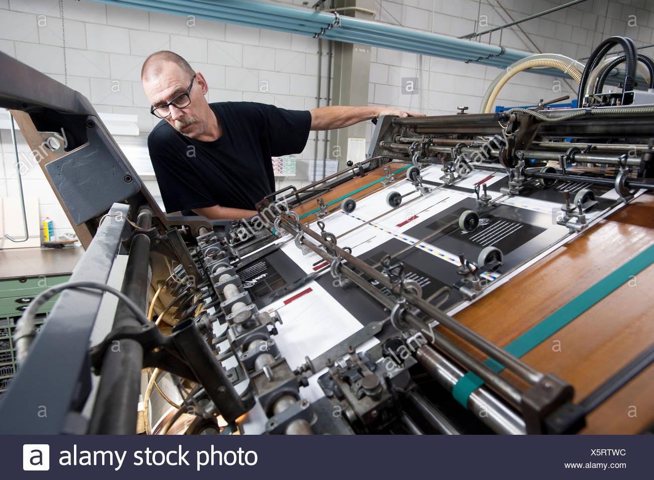 Worker monitoring print machine in printing workshop - Stock Image