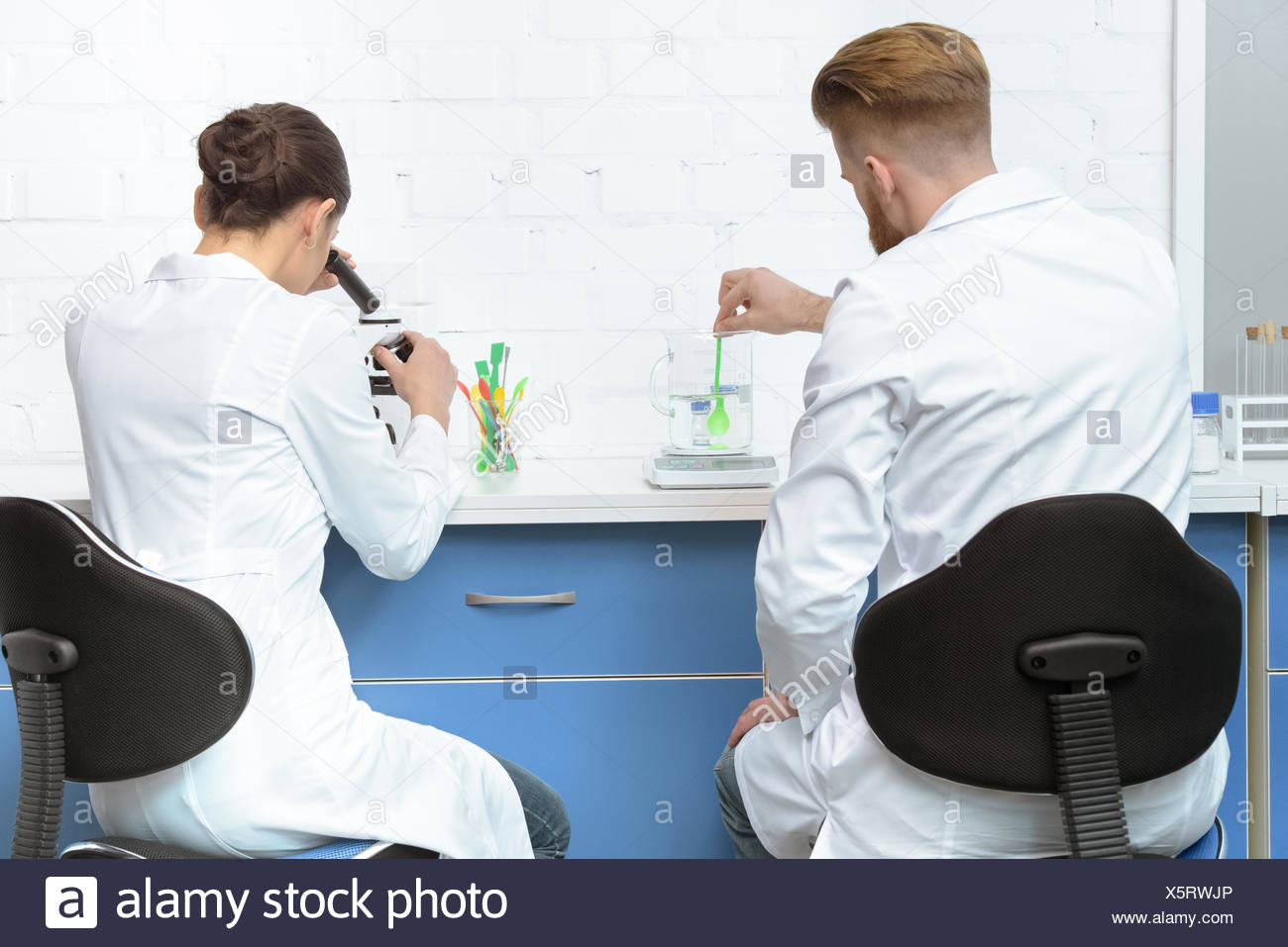 back view of scientists working with chemicals in lab - Stock Image