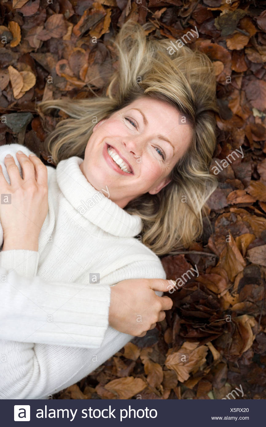 Smiling woman lying on autumn leaves. - Stock Image