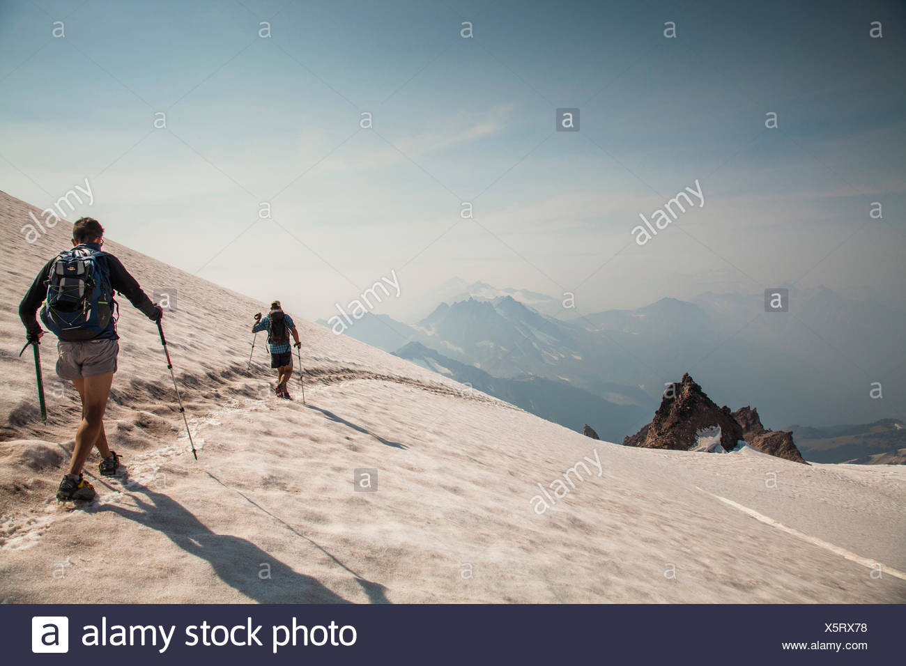 Two climbers descend a snowfield after climbing Glacier Peak in the Glacier Peak Wilderness in Washington. - Stock Image