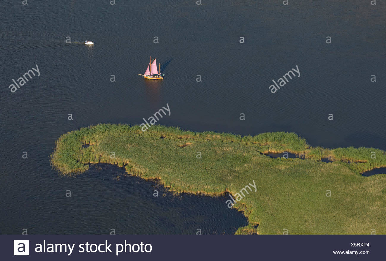 Aerial view, flat-bottomed boat and a sailing ship in Barther Bodden lagoon off Grosser Kirr Island - Stock Image