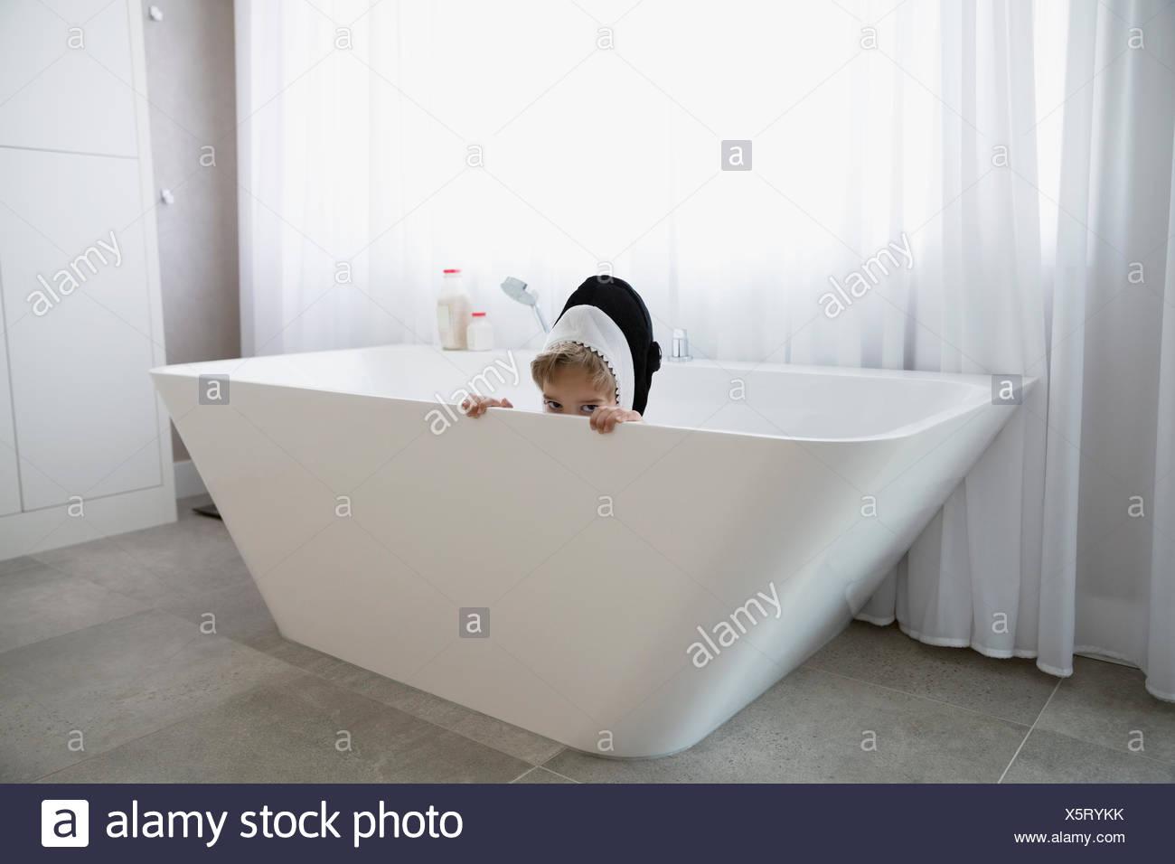 Portrait shy boy in killer whale costume hiding in bathtub Stock ...