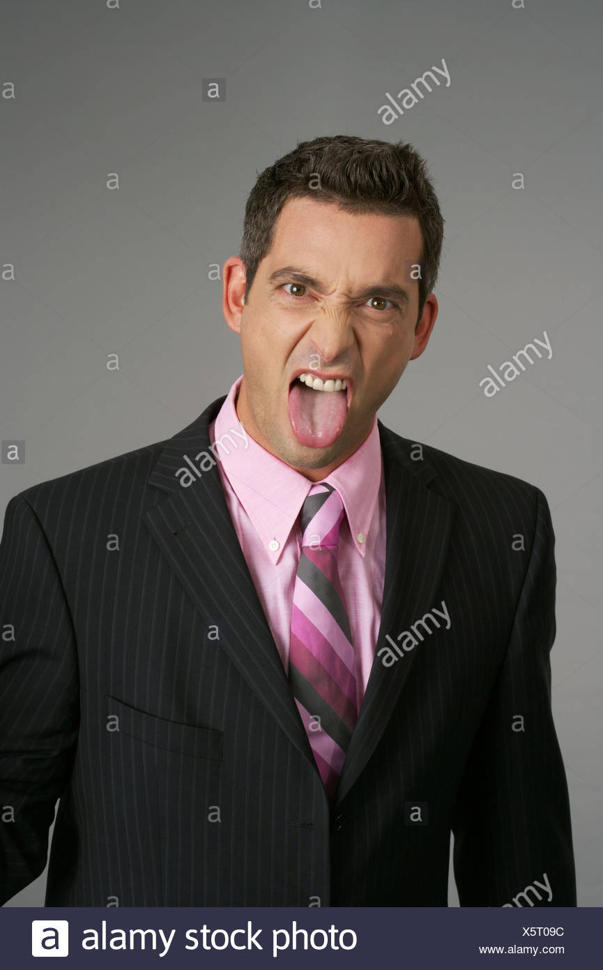 Businessman sticking out his tongue - Stock Image