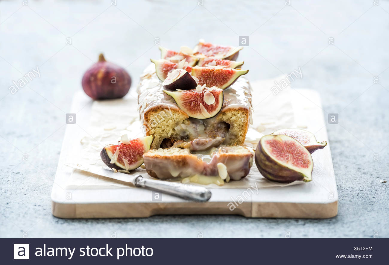 Loaf cake with figs, almond and white chocolate on white serving board over grunge background, selective focus - Stock Image