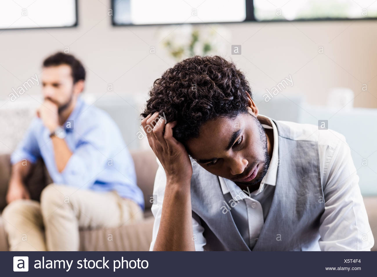 Troubled man sitting in foreground - Stock Image