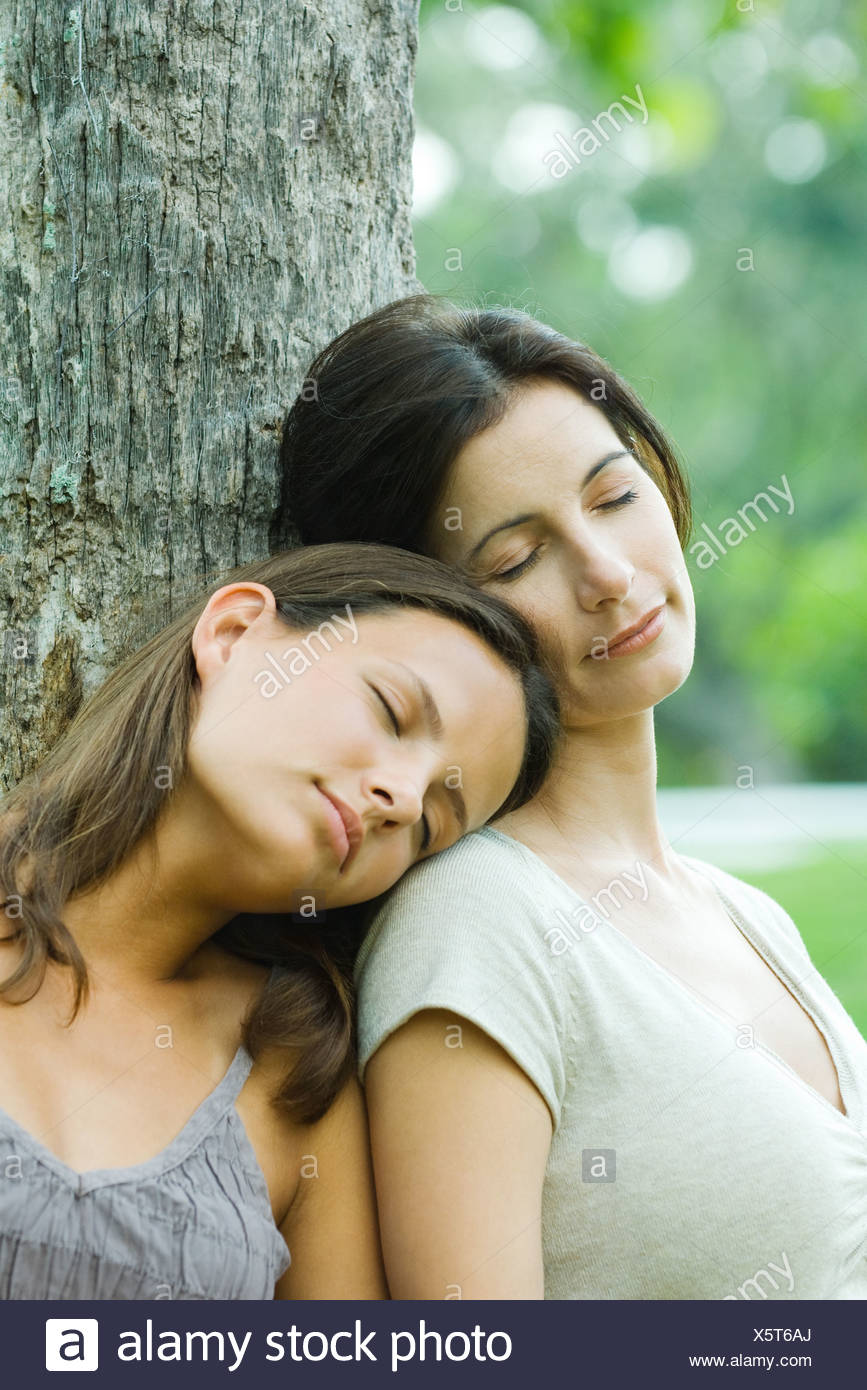 Mother and teen daughter leaning against tree with eyes closed, daughter's head on mother's shoulder Stock Photo