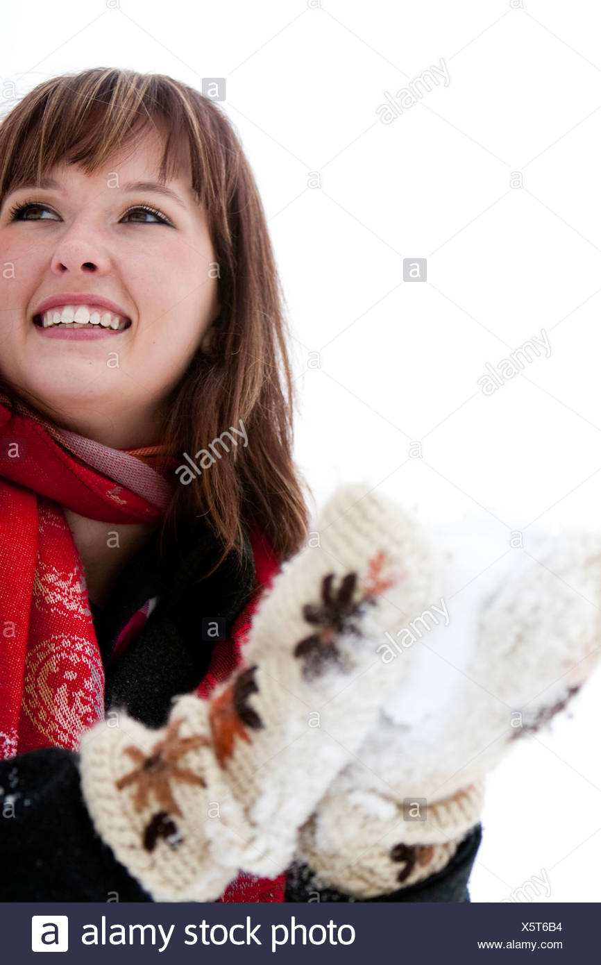 A woman wears a red scarf and packs a snowball with big fuzzy knitted mittens on an overcast winter day, in Fort Collins, Colora - Stock Image