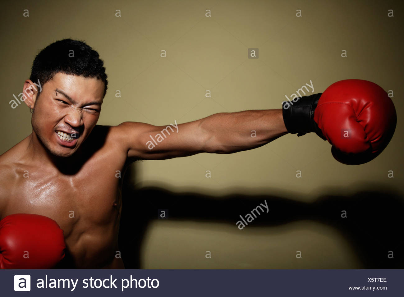 man punching the air with red boxing glove - Stock Image
