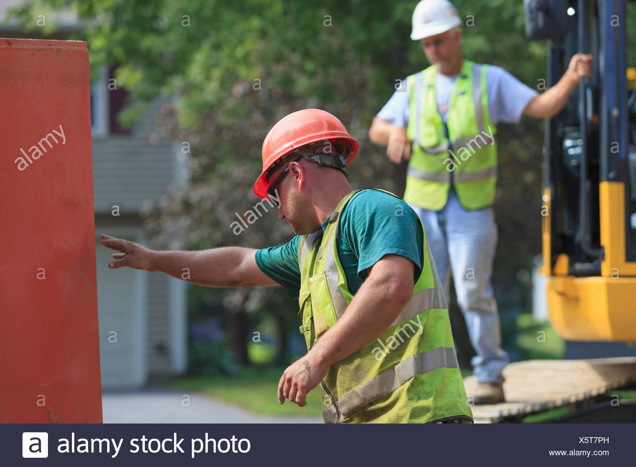 Construction worker directing placement of shoring - Stock Image